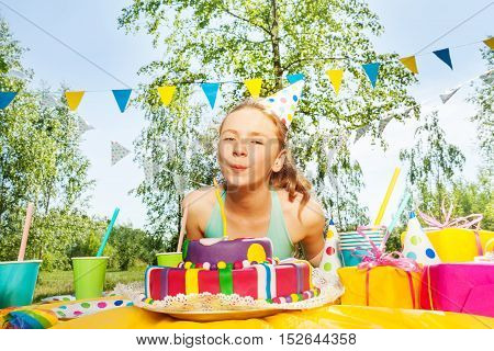 Portrait of happy young girl, blowing candles on birthday cake, at the outdoor birthday party