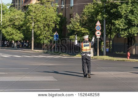 Traffic Policeman Directing Cars In A Crossing Road