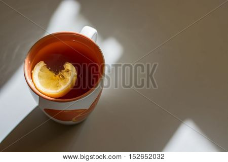 Cup of tea. Sun rays falling from the window. Natural light. Close up.