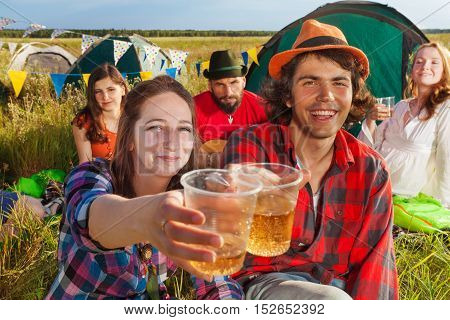 Portrait of happy young people clanging glasses among friends at camping