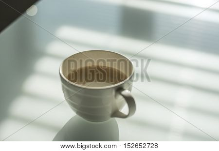 Cup of coffee on the white glass table. Reflections and shadows. Conceptual modern office.