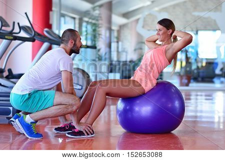 Personal Trainer Training A Woman In The Gym With Yoga Ball
