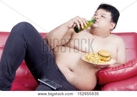 Portrait of lazy fat man is enjoying fresh beer and junk food on the red couch while watching tv isolated on the white background