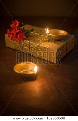 Two illuminated Indian earthen lamps and elegantly wrapped gift box and flower. Diwali is the biggest Hindu festival celebrated in India.