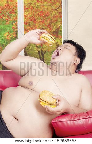 Overweight man sitting on the couch while eating two big hamburgers with autumn background on the window