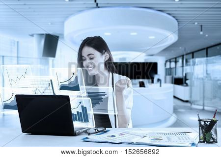 Image of happy business woman sitting and looking at virtual graphic screen in the office with laptop and paperwork on the table