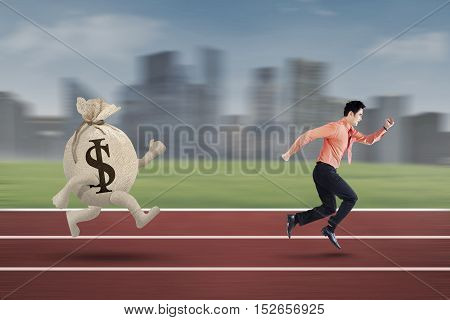 Young entrepreneur is being chased by a bag of dollar on the track