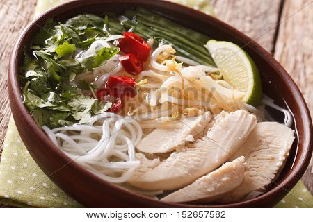 Vietnamese Food: Spicy Soup Pho Ga With Chicken, Rice Noodles And Herbs Close-up. Horizontal