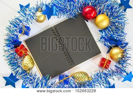 Christmas or New year flat composition. Blue sparkling wreath. Fir tree toys. Black paper notebook with blank page. Seasonal decor mockup for greeting message or citation. Festive background