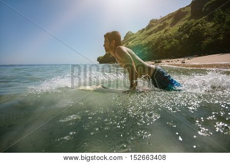 Side view shot of young man doing water surfing in sea. Male surfer in the ocean water with surf board.