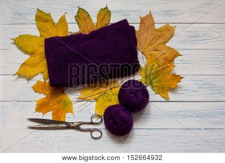 Violet yarn knit fabric knitting needles scissors and fallen leaves are on white vintage wooden desk. Top view.