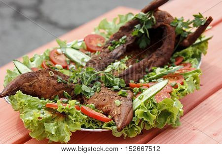Smoked rabbit meat with lettuce and tomato slices on a wooden table