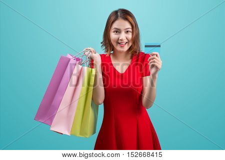 Santa asian woman holding shopping bags and credit card against blue background.