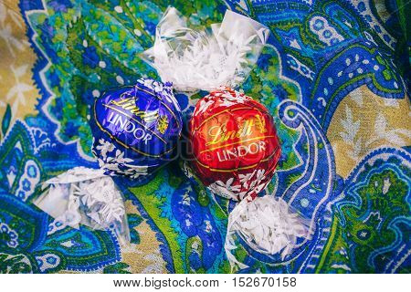 KILCHBERG SWITZERLAND - MAR 20 2014: Tasty red Lindt Lindor chocolate on a colored silk background Lindt & Sprüngli AG more commonly known as Lindt is a Swiss chocolatier and confectionery company founded in 1845 and known for their chocolate truffle ball