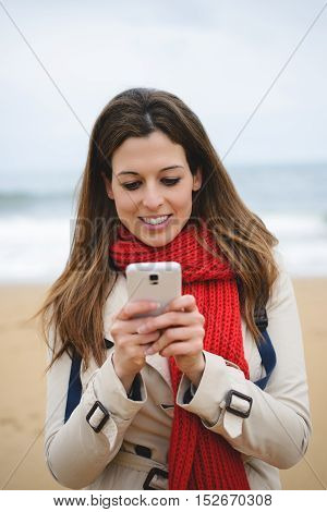 Cheerful Woman Texting On Smartphone At The Beach On Autumn