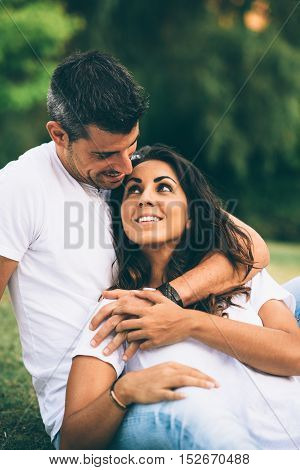 Young loving affectionate couple dating and enjoying their love at the park on summer or spring.