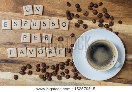 Un espresso per favore (in italian An espresso please) concept on wood.