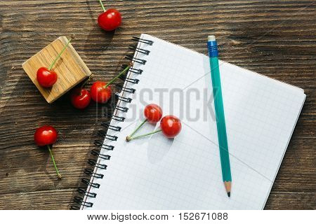 Green graphite pencil fresh red cherry spiral paper notebook and block on wooden background