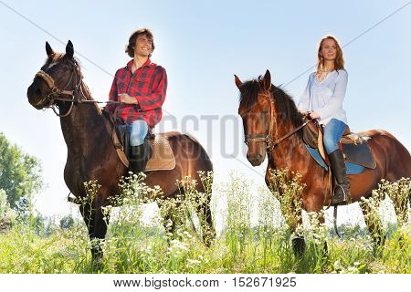 Portrait of happy young couple horseback riding in flowery meadows