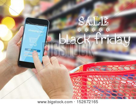 hands holding and pointing mobile smart phone with mobile shop on comercial center blur background and black friday sale words