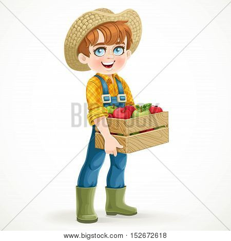 Cute boy farmer in jeans overalls and rubber boots holding a wooden box with apple isolated on white background