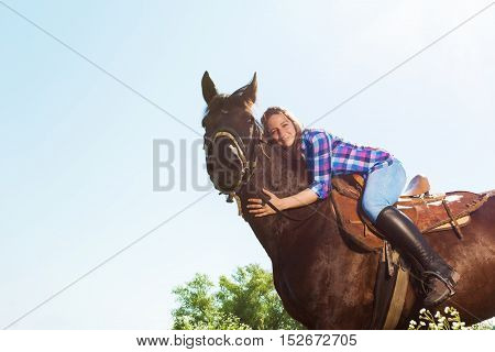 Outdoor portrait of happy young woman hugging her chestnut brown horse