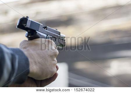 Gun Fire Street Assault. Shooting a Handgun and Smoke Coming out of Barrel.