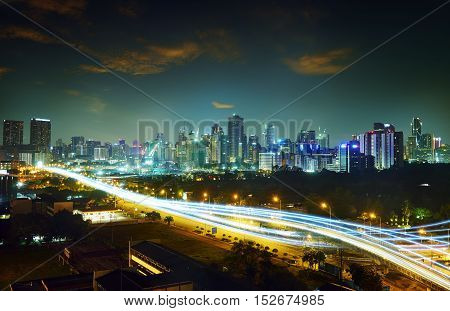 Abstract and car lighttrail background city skyline downtown background and highway interchanged nigh view .