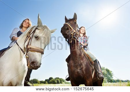 Close-up portrait of two happy women riding beautiful purebred horses outdoor