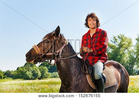 Portrait of happy equestrian riding his horse in summer field