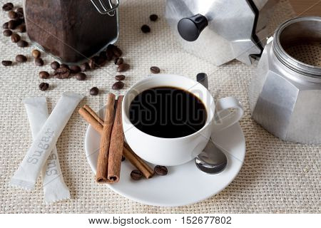 Black coffee with italian coffee pot, beans and cinnamon. Cup of black coffee with italian coffee pot on flax fabric, top view.