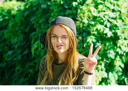 Young girl with pretty expressive sexy face with brown hair in black baseball cap showing rock devil horns gesture on green leaves background outdoor