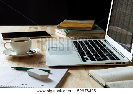 Home workplace desk with laptop, books and coffee. Home office working place with laptop, cup of coffee, notebook, textbooks,books, tablet on wooden table with dark background.