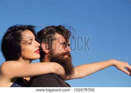 Pretty girl young beautiful woman with red lips and short brunette hair hugs handsome man hipster with long beard and moustache on blue sky