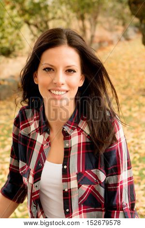 Beautiful brunette girl taking a walk by a park in autumn