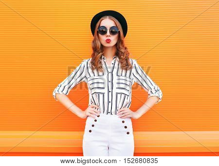 Fashion Pretty Glamour Woman Wearing A Black Hat Sunglasses White Pants Over Colorful Orange Backgro