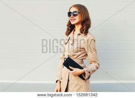 Fashion Pretty Smiling Woman Model Wearing A Coat And Black Handbag Clutch Over Grey Background