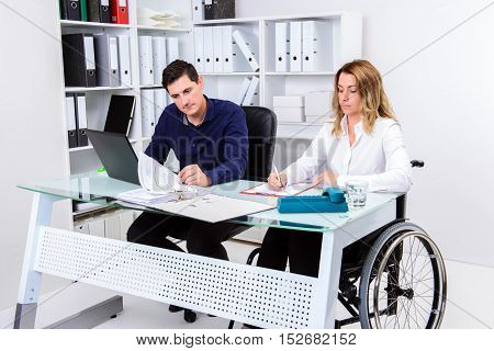 Disabled Businesswoman In Wheelchair And Her Colleague
