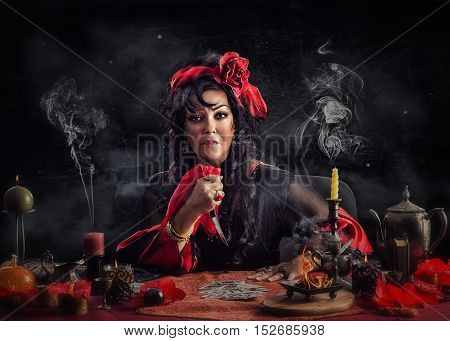 Gypsy hag doing deadly curse ritual with a knife and playing cards. Mature cron wearing red-black dress sits at the desk surrounded smoking candles on black grange background