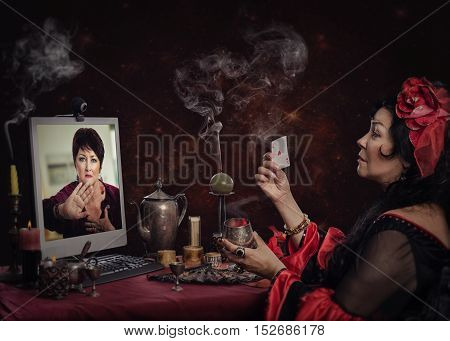 Irritated woman asks gypsy cartomancer to stop online divination session. She either does not trust this fortune-teller or does not want to know future from her.  Sitting gypsy seer holds one card by hand and looks at her client on the monitor