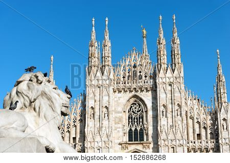 Facade of the Duomo di Milano (Milan Cathedral 1418-1577) and lion statue. Church monument symbol of Lombardy and of Italy