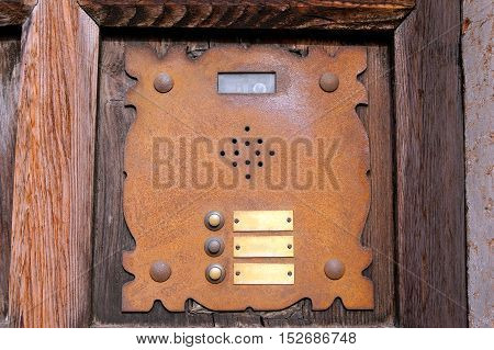 Detail of an old rusty interphone with three doorbell buttons and video camera on a wooden door. Verona Italy