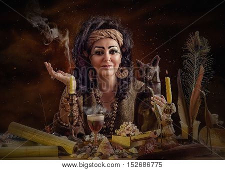 Portrait of female Egyptian diviner posing with cat figurine and occult items. The mature black haired soothsayer sits at the desk attentively looks at the camera