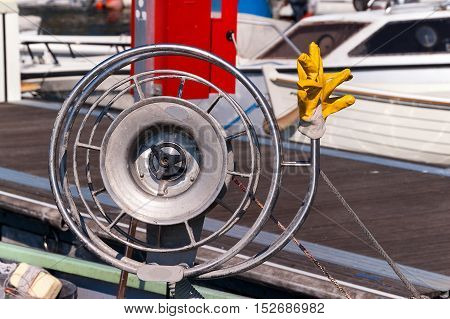 Detail of a fishing boat with a metallic winch for fishing net with ropes and yellow work gloves