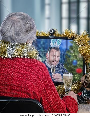 Mature dude wearing a bunny ears wishes gray-haired senior woman in red jacket a Merry Christmas and offers a toast with white sparkling wine during internet video chat