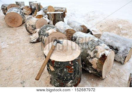 Axe On A Chunk Of Firewood In The Snow