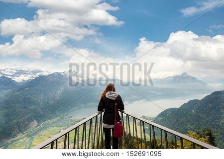 Woman traverler looking aerial view of the city district and Interlaken from viewpoint at Harder Kulm in Interlaken Bern Switzerland.