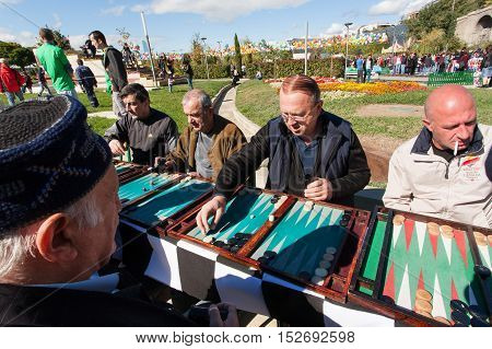 TBILISI, GEORGIA - OCT 16, 2016: Elderly men playing backgammon in a park during annual autumn city festival Tbilisoba on October 16, 2016. Tbilisi has a population of 1.5 million people