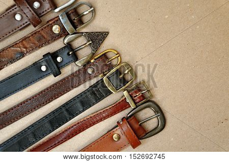 Fashion background. Vintage brown leather belts with metal rusty buckle on beige cardboard surface located diagonally closeup.