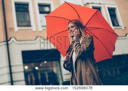 Good talk with friend. Low angle view of attractive young smiling woman carrying umbrella and talking on the mobile phone while walking down the street